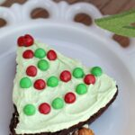 Easy Christmas Tree Brownie Treats! Bake brownies in a round pan, cut into wedges, top with green frosting and Mini M&Ms for lights and add a pretzel for the tree trunk!