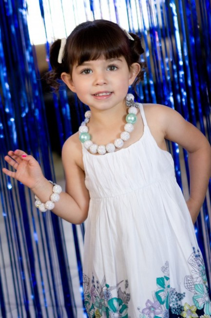 Birthday girl in front of icicle photo backdrop - Disney Frozen Birthday Party Ideas