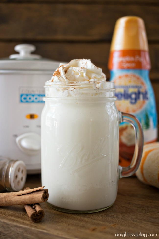 A large mug is filled with white liquid and topped with whipped creme. The mug is surrounded by ingredients such as cinnamon sticks and creamer, and a crock pot sits in the background.