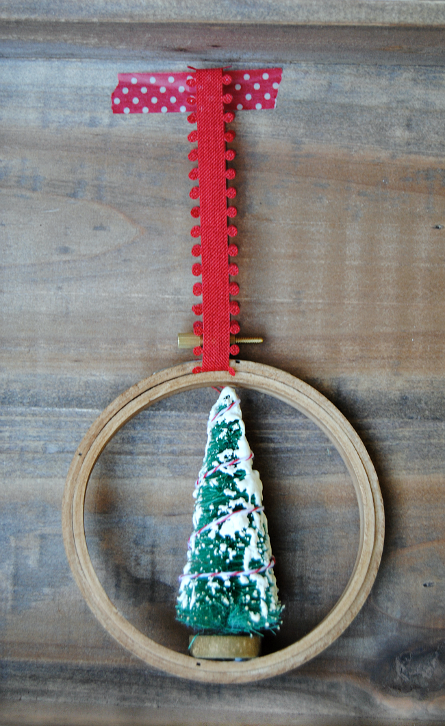 Trim your tree with these easy Embroidery Hoop Christmas Ornaments! Add a bottle brush tree and a red ribbon to a faux stained embroidery hoop for a charming DIY ornament!
