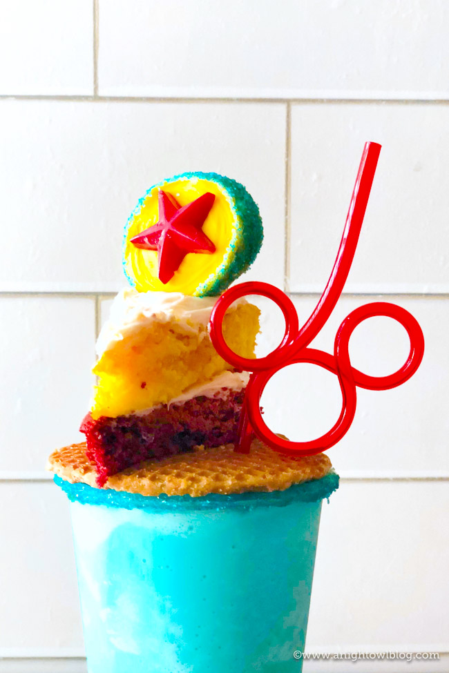 Topped with a Pixar Inspired Cookie Pop and a homemade Pixar Lemon-Raspberry Cake, this Pixar Fest Inspired Freakshake is a festive way to bring the fun of Disneyland's Pixar Fest home! #Disneyland #PixarFest