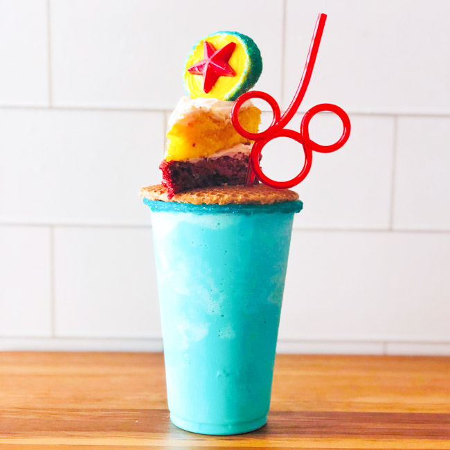 Topped with a Pixar Inspired Cookie Pop and a homemade Pixar Lemon-Raspberry Cake, this Pixar Fest Inspired Freakshake is a festive way to bring the fun of Disneyland's Pixar Fest home! #Disneyland #PixarFest