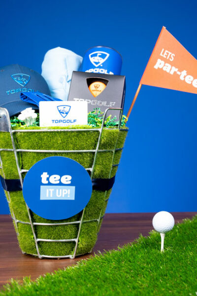 """Perfect for the golf lover in your life, whip up a """"Tee It Up"""" Golf Gift Basket with Evite And Topgolf!"""