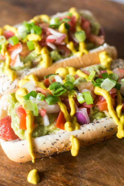 These Easy Sonoran Hot Dogs add a little Southwestern flair to your frank with pinto beans, guacamole, pico de gallo and more!